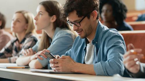 Студент устанавливает мобильное приложение во время интересной лекции
